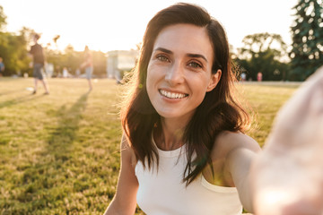 Image of smiling middle-aged woman taking selfie photo while sitting on grass in summer park