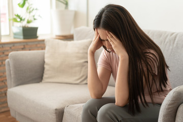 Asian woman are holding their hands to the head in pain on the sofa at home, Young women have severe headaches from migraines, Health and illness concept Fototapete