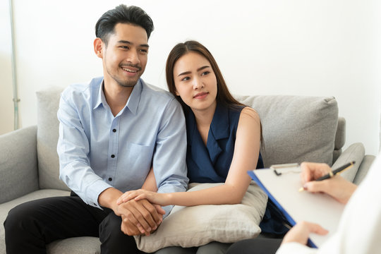 Asian couple join hand to encourage while sitting on the couch in the psychiatrist room to consult mental health problems by doctor, Health and illness concepts