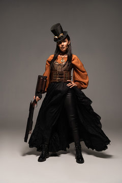 full length view of attractive steampunk woman holding guy on grey