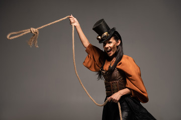 attractive steampunk girl in top hat holding lasso and screaming isolated on grey