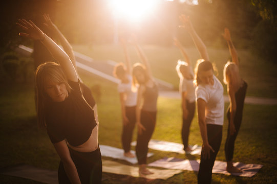Group of women do yoga in city park on summer sunny sunrise or sunset. Group of people are tilting to the side with their hands up