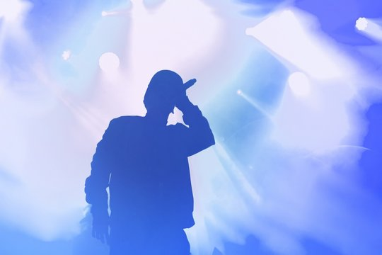 Young hip hop singer on stage in music hall.Silhouette of rapper with microphone in hand performing live set on concert stage in nightclub.Rap artist with mic in bright blue stage lights singing song