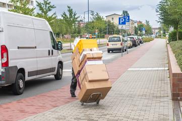 Ein Angestellter eines Paketdienstes liefert Pakete aus