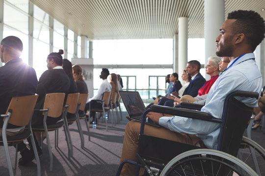 Disabled young businessman using laptop during seminar