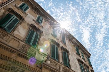 Italian renaissance windows with shutters. Sun flair and blue sky. Ferrara, Italy.