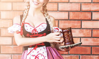 Beautiful woman in dress for Octoberfest with a glass of beer.
