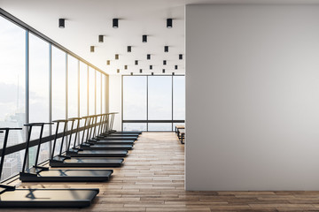 White blank wall in modern gym with wooden floor