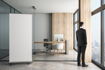 Blank white poster on concrete floor in modern loft style office and businessman