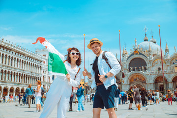 smiling couple holding italian flag venice central square san marco