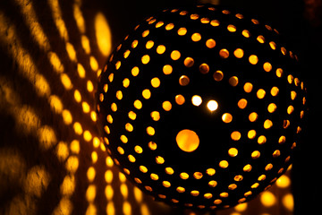 Coconut shell lamp with holes casting spotty yellow orange color round light pattern on the wall