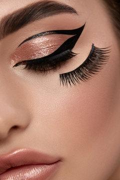 art of make-up artist with false eyelashes and black eyeliner