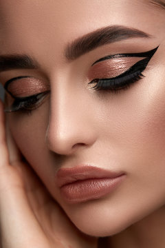 luxury woman make-up with golden shadow and black eyeliner