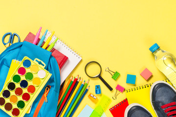 School backpack with stationery on yellow background.