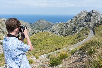 Teen takes pictures of the panorama of the island of Mallorca