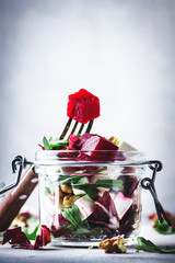 Beet and cheese healthy salad with arugula and walnuts, trendy salad jar, gray kitchen table, place for text, selective focus