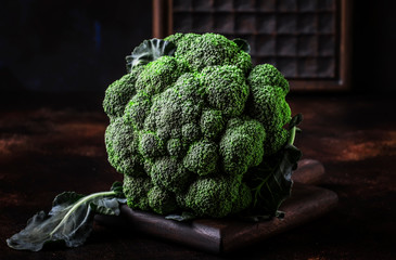 Big head of fresh green broccoli on dark rustic background, selective focus, minimalism