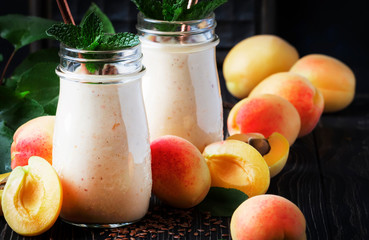Apricot smoothies with fruits and flax seeds in glass bottles, dark rustic kitchen table background, place for text, selective focus