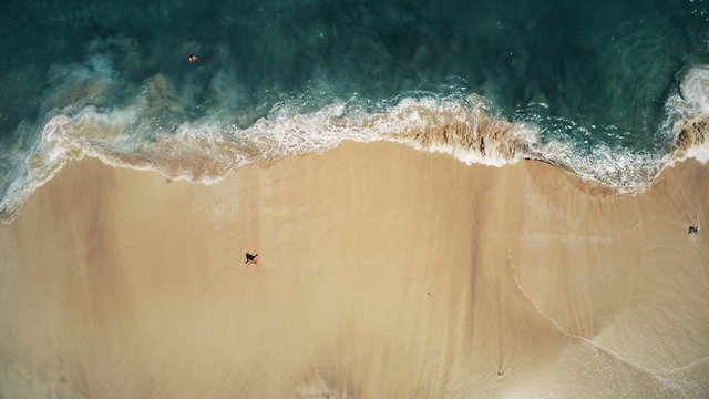 Aerial Top Drone View on Ocean Waves and White Sand Beach. Crystal Water Landscape in Tropical Bali Island, Indonesia. People Walk, Swim and Relax. Cinematic Filter Toning