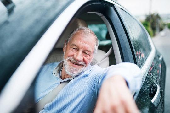 Happy senior man sitting in car in driver seat.