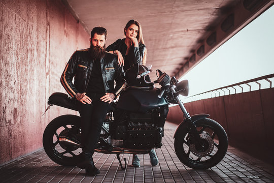 Beautiful young couple is chilling in the tunnel with motorbike.