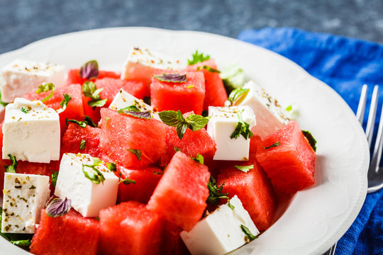 Watermelon salad with feta cheese and herbs in a white plate on blue background.