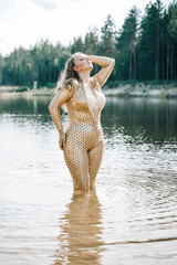 In de dag UFO Woman with plus size curvy body in golden futuristic outfit posing in the water
