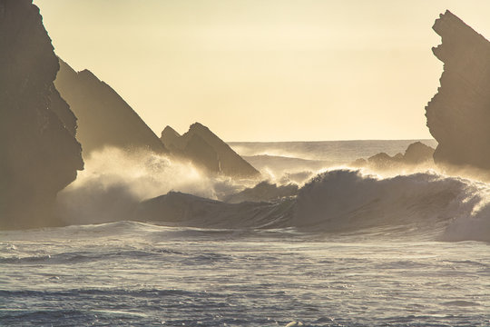 Waves crashing on Portugal coastline at sunset