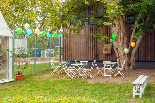 Place for children birthday party front or back yard with hanging decorative multi-colored balloons, white tables and chairs, bench near a wooden house in green autumn grass