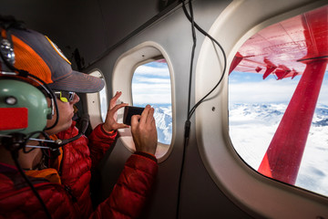 A woman is taking a photo of the Alaska Range with a smart phone out the window of a plane over Denali National Park, USA
