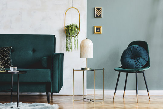 Design composition of living room interior with green velvet sofa and chair, stylish coffee table, marble table lamp, pillow, hanging flowerbed, plants and elegant accessories. Modern home decor