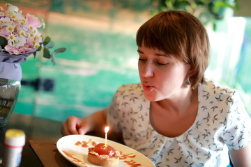 Woman blows out candle on cake