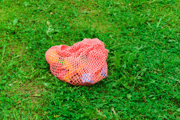 Fotobehang Coral string bag with toys on the grass. Zero waste concept.