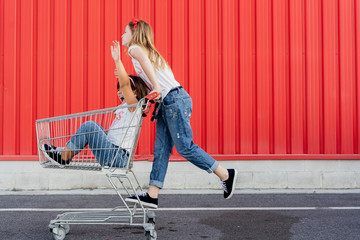 Sisters with shopping cart in front of red wall