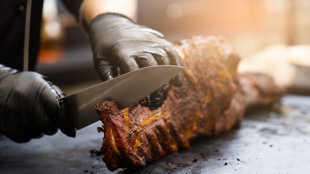 Grill restaurant kitchen. Chef in black cooking gloves using knife to cut smoked pork ribs.