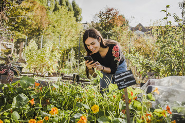 Happy young woman taking pictures with smartphone in urban garden