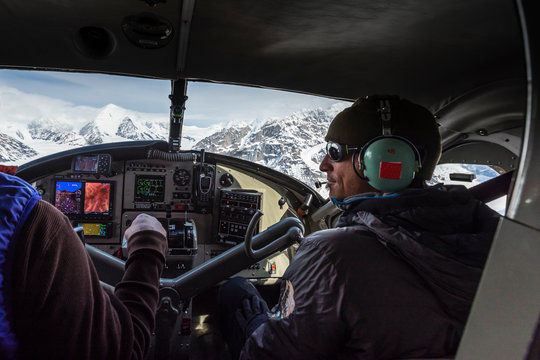 A man in the copilot seat of a small plane above the Alaska Range of mountains over Denali National Park, USA