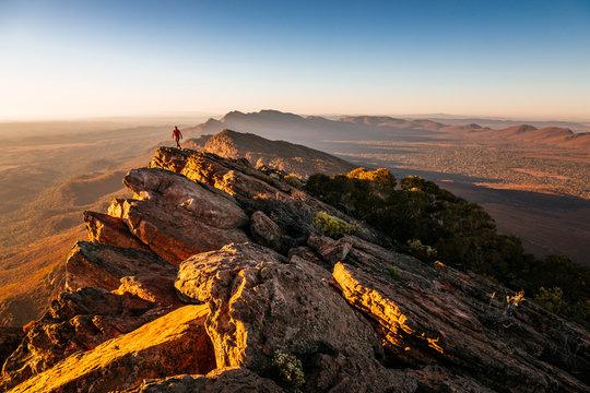 Woman walking on cliff at St Mary Peak during sunrise, Australia