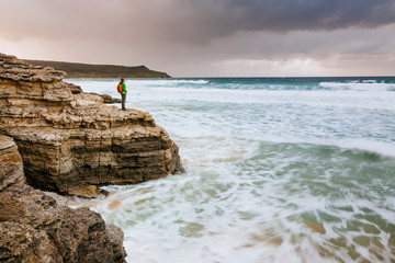 A woman stops at a rocky headland on a stormy day on the Cape Queen Elizabeth Walk, Bruny Island, Tasmania, Australia
