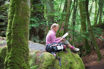 Germany, Rhineland Palatinate, Eifel Region, South Eifel Nature Park, View of woman hiker sitting on bunter rock formations at beech tree forest