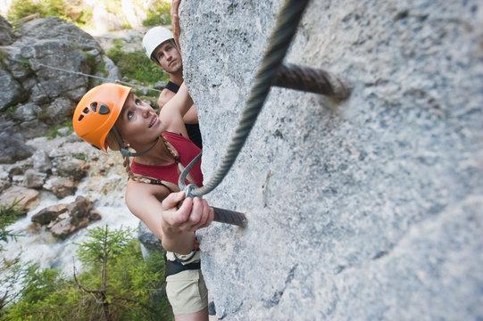 Austria, Steiermark, Ramsau, Silberkarklamm, Young couple climbing rock, looking up