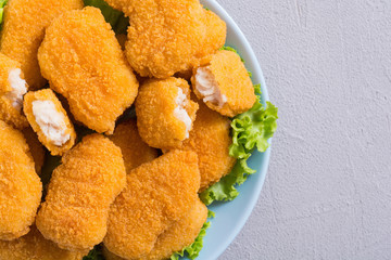 Chicken nuggets in plate on rustic background