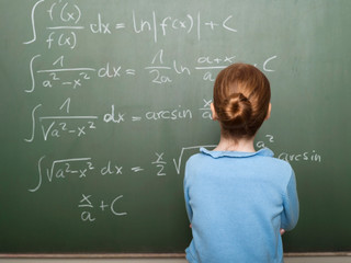 Girl (6-7) standing in front of blackboard,solving arithmetic problem,rear view