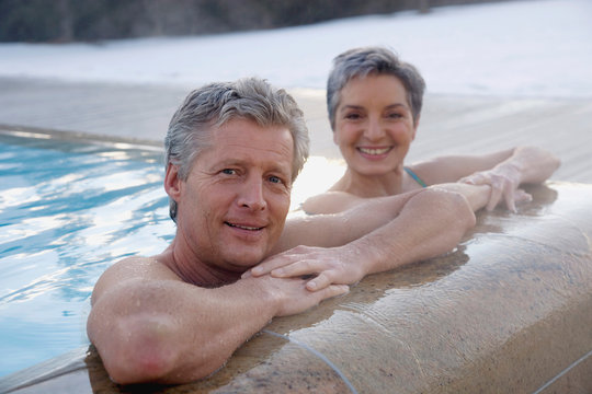 Mature couple relaxing in outdoor spa, portrait