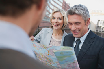 Germany, Hamburg, Business people holding city map, smiling, portrait
