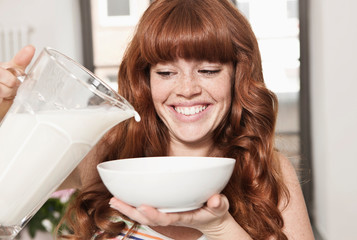 Germany, Berlin, Close up of young woman preparing cereals, smiling