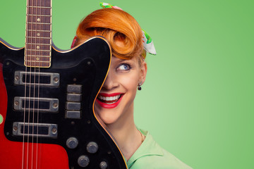 pinup girl with electric acoustic rock guitar smiling
