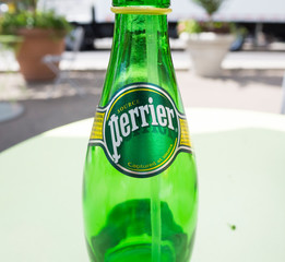 New York, New York, USA - June 7, 2012: An empty bottle of Perrier water with a straw sits on a table outdoors in New York City.