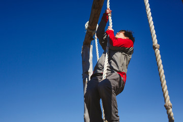 A focused man climbs to the top of a rope against a blue sky