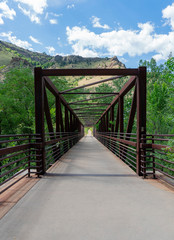 Metal Beam Footbridge Across Creek with Mountains and Blue Sky with Clouds